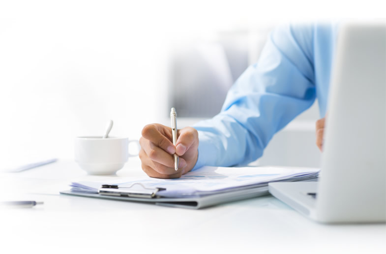 Photo of man writing at a desk